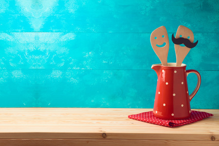 Kitchen cute utensils in red jug on wooden table. Cookng and baking concept background