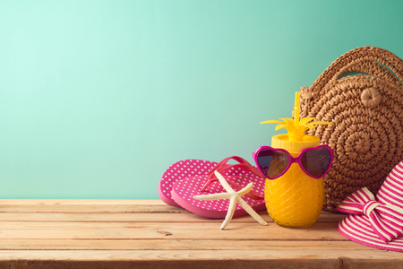 Summer holiday vacation background with pineapple juice, beach fashion bag and flip flops on wooden table 写真素材