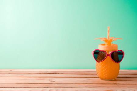 Summer vacation background with cute pineapple juice and sunglasses on wooden table 写真素材
