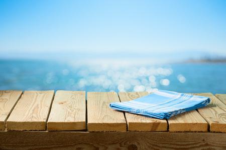 Mesa de madera vacía con mantel sobre fondo de playa de mar