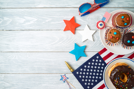 Happy Independence Day, 4th of July celebration concept with cupcakes, donuts and american flag on wooden background. Top view from above