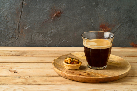 Coffee cup and small caramel nut tart on wooden table