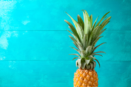 Summer concept with pineapple over blue wooden  background