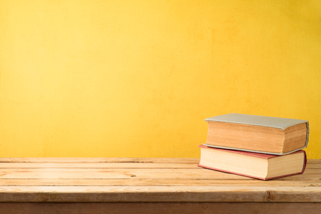 Old books on wooden table over yellow wall background