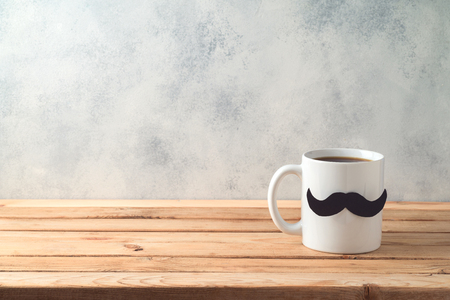 Happy Fathers day concept with coffee mug and mustache over wooden background