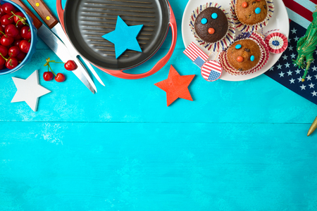 Happy Independence Day, 4th of July celebration concept with cupcakes, barbeque grill and american flag on wooden background. Top view from above