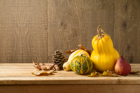 Autumn harvest background with pumpkin and squash on wooden table. Thanksgiving holiday concept