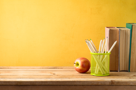 Back to school background with pencils, apple and old books on wooden table over yellow wall 写真素材