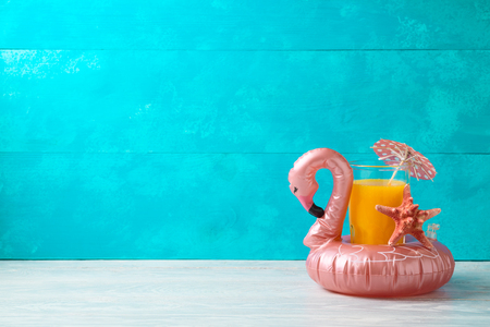 Summer vacation background with orange juice and flamingo pool float on wooden table