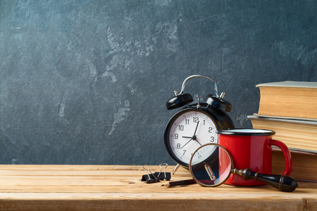 Back to school background with coffee cup, alarm clock and old books on wooden table 写真素材