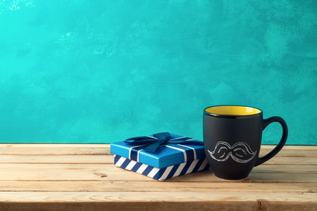 Happy Fathers day concept with coffee mug and gift box over wooden background 写真素材