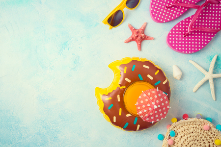 Summer holiday vacation background with orange juice and beach accessories. Top view from above