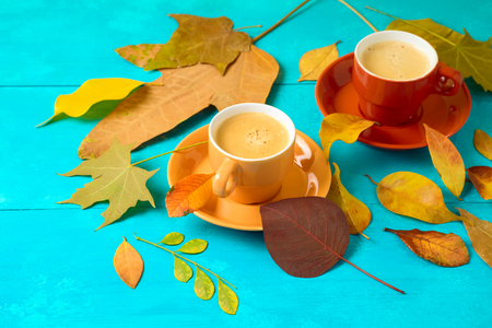 Coffee cup and fall leaves on wooden table. Autumn concept