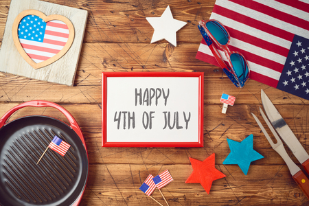 Happy Independence Day, 4th of July celebration concept with frame, USA flag and barbeque grill  on wooden background. Top view from above 写真素材