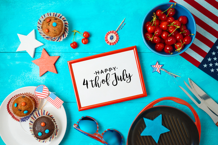 Happy Independence Day, 4th of July celebration concept with frame, cupcakes and barbeque grill  on wooden background. Top view from above 写真素材