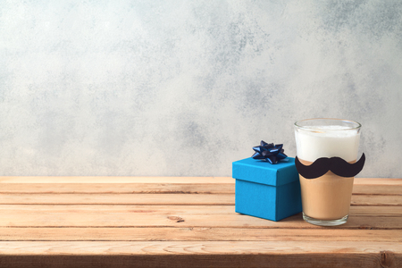 Happy Fathers day concept with latte macchiato coffee and gift box over wooden background