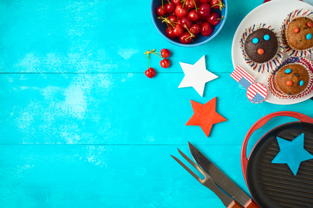 Happy Independence Day, 4th of July celebration concept with cupcakes and barbeque grill  on wooden background. Top view from above