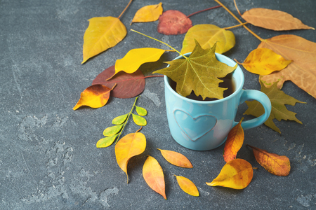 Cup of tea and fall leaves on blackboard table. Autumn concept 写真素材