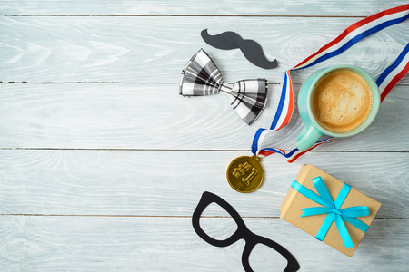 Happy Fathers day concept with coffee cup, competition medal and gift box over wooden background. Top view from above 写真素材