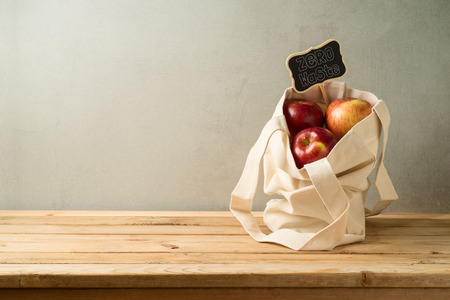 Zero waste lifestyle and shopping concept with cotton bag and apples on wooden table