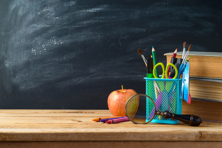 Back to school background with school supplies, apple and old books on wooden table over chalkboard