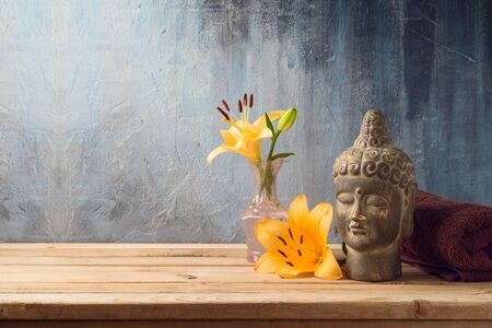 Buddha statue, flowers and towel on wooden table over dark background