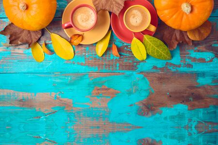 Autumn background with coffee cups, fall leaves and pumpkin on wooden table. Top view from above 写真素材