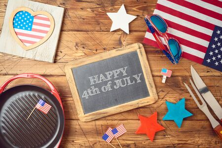 Happy Independence Day, 4th of July celebration concept with chalkboard, USA flag and barbeque grill  on wooden background. Top view from above 写真素材