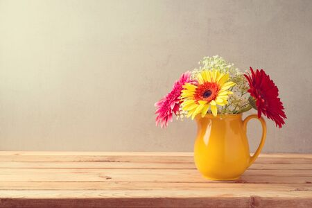 Colorful flower bouquet in yellow jug on wooden table.