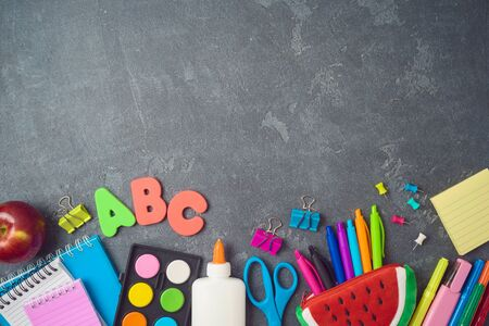 Back to school background with school supplies on blackboard. Top view from above