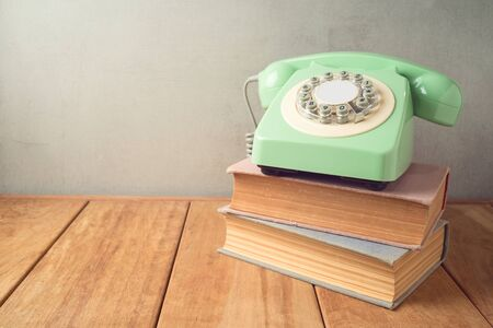 Retro telephone and old books on wooden table 写真素材