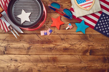 Happy Independence Day, 4th of July celebration concept with USA flag and barbeque grill  on wooden background. Top view from above