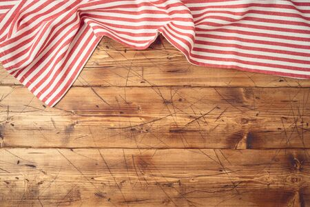 Wooden tabletop with striped tablecloth for kitchen or cooking food background. Top view from above