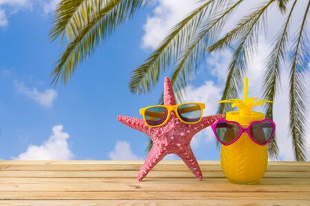 Summer vacation concept with cute starfish and pineapple juice with sunglasses over sea beach background