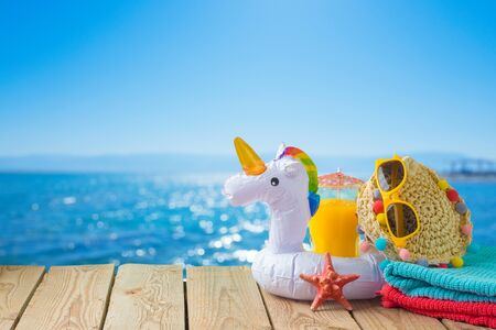 Summer vacation concept with orange juice, beach accessories and unicorn pool float over sea beach background