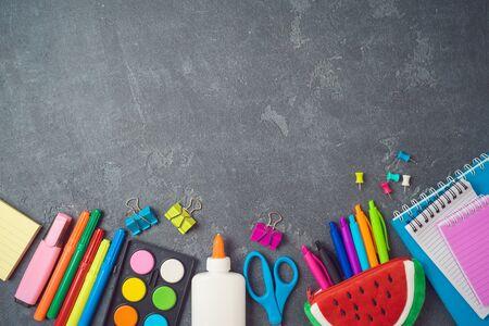 Fondo de regreso a la escuela con útiles escolares en la pizarra. Vista superior desde arriba