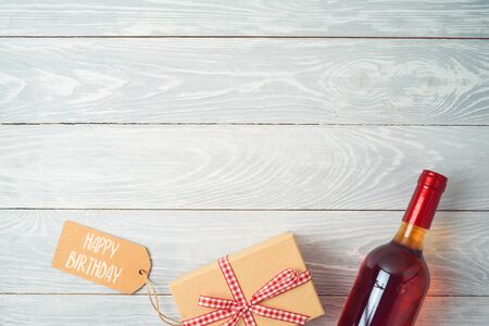 Gift box, bottle of wine and gift tag on wooden table background. Top view from above