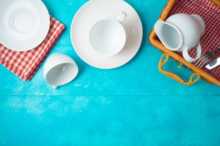 White dishes and tableware on blue wooden background. Picnic concept. Top view from above