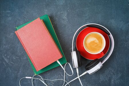 Audio book concept with old book, headphones and coffee cup over blackboard background. Top view from above