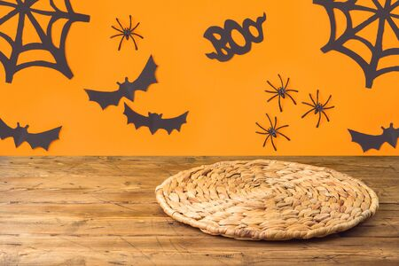 Halloweeen background with empty wooden table and wicker round placemat