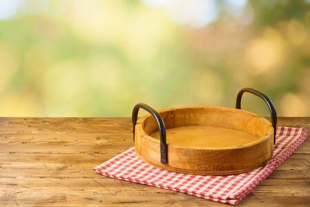 Leeres Holztablett mit rot karierter Tischdecke auf Holztisch über herbstlichem Bokeh-Hintergrund Standard-Bild