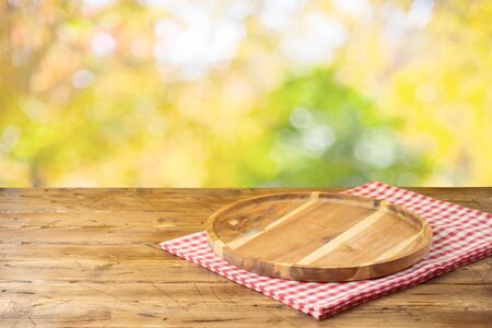 Empty wooden table with tablecloth and wooden board over autumn nature park background Reklamní fotografie