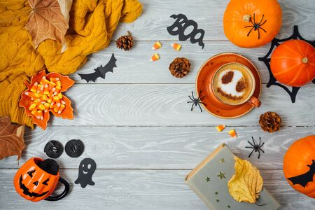 Halloween holiday background with coffee cup, pumpkin and autumn leaves on wooden table. Top view from above. Flat lay Фото со стока