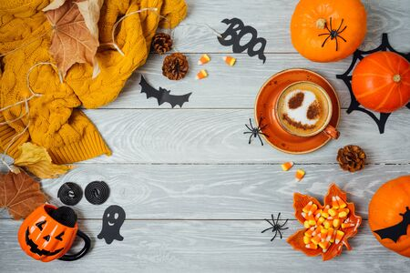 Halloween holiday background with coffee cup, pumpkin and autumn leaves on wooden table. Top view from above. Flat lay Stockfoto