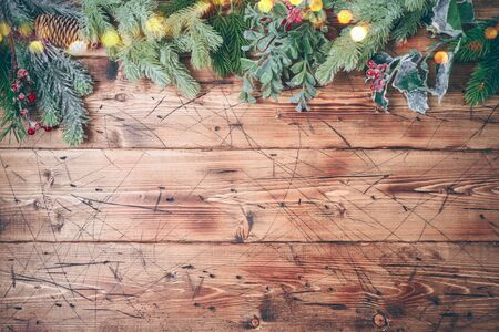 Christmas background with fir tree branches decorations on wooden table. Top view from above