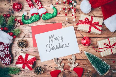 Christmas greeting card with gift boxes, santa hat and  decorations on wooden background. Top view from above