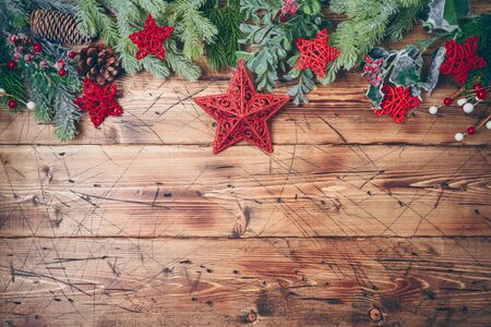 Christmas background with fir tree branches and red stars decorations on wooden table. Top view from above Фото со стока - 131364017