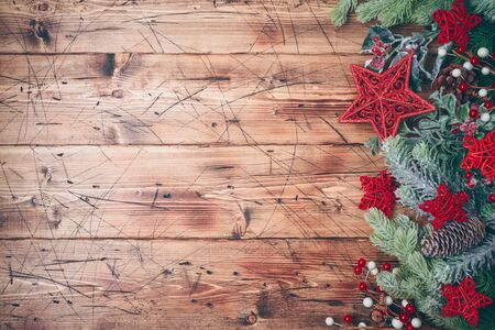 Christmas banner with fir tree branches and red stars decorations on wooden background. Top view from above Фото со стока - 131363669