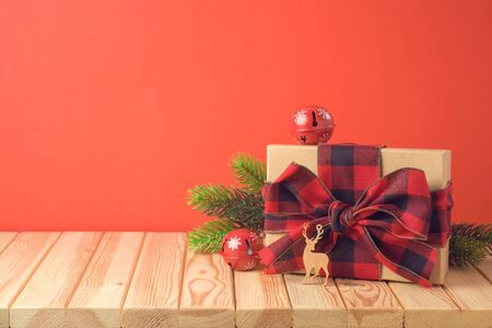 Christmas holiday celebration concept with gift box and pine tree branches on wooden table. Imagens