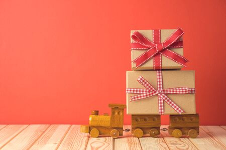 Holiday celebration concept with gift boxes on toy train on wooden table.
